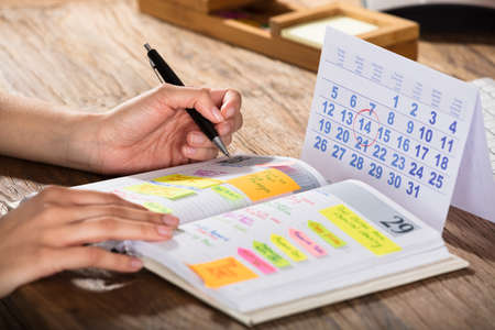 Primer plano, de, un, hombre de negocios, con, calendario, escritura, horario, en, diario, en, escritorio