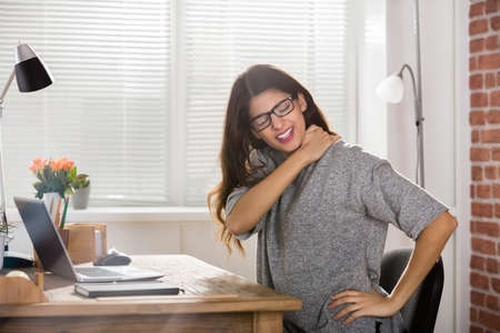 Young Attractive Businesswoman Having Neck Pain In Office
