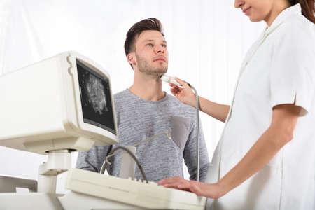 Joven, hombre, obteniendo, ultrasonido, exploración, cuello, joven, hembra, doctor, clínica