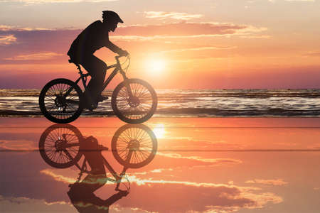 Silhouette Of A Cyclist At Beach With Dramatic Sky During Sunset photo