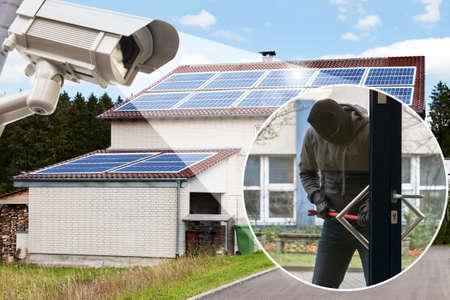 Macchina fotografica del CCTV che mostra burglar che prova ad aprire una serratura della porta di fronte a casa