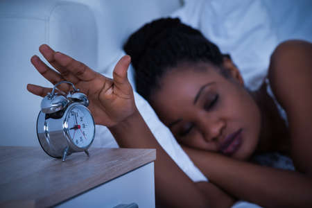 Woman Sleeping On Bed Turning Off The Alarm Clock