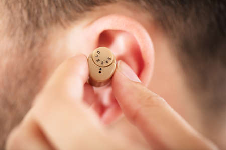 Close-up Of A Person Putting Hearing Aid On Mans Ear
