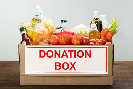 canned goods: Donation Box Full Of Groceries On Table