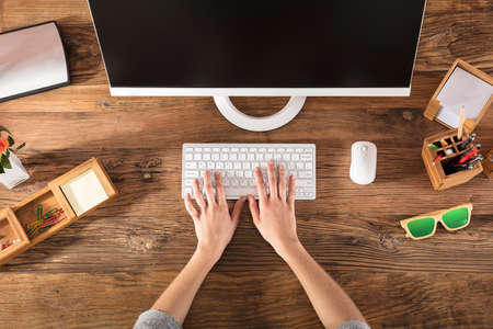 Elevated View Of A Person's Hand On Keyboard At Workplace