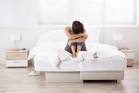 contemplated: Contemplated Young Woman Sitting On Crumpled Bed In Bedroom