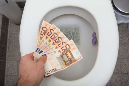 Elevated View Of A Man's Hand Throwing Fifty Euro Notes In Toilet