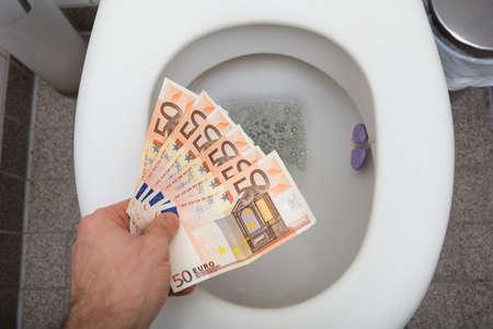 トイレで 50 ユーロ紙幣を投げる人の手の立面図 写真素材