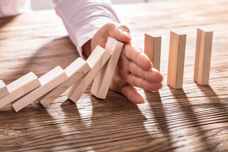 Close-up Of A Business Woman's Hand Stopping Falling Blocks On Wooden Table Stock Photo
