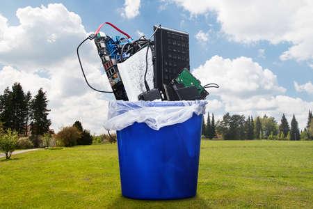 Beschädigte Hardware-Ausrüstung im blauen Mülleimer auf Rasen Standard-Bild
