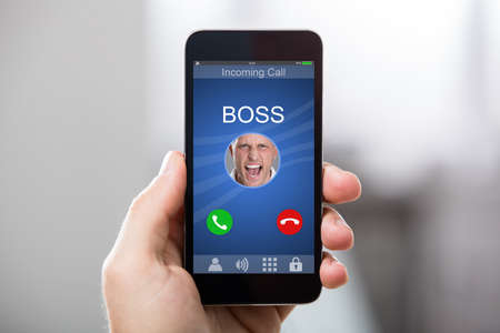 answer: Close-up Of A Hand Holding Smart Phone With Bosss Incoming Call On Display