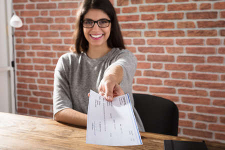 Smiling Young Woman Offering Company Cheque At Workplace