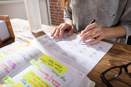 Plan rapproché d'une femme d'affaires Calendrier de marquage sur calendrier à partir d'un journal sur le lieu de travail