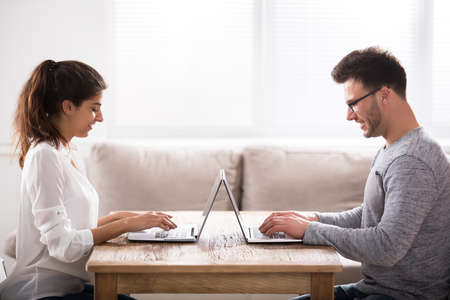 Happy Young Couple Sitting Face To Face Using Laptop Over The Table At Home