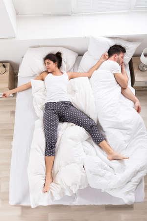 Bovenaanzicht van jonge vrouw slapen naast haar man op bed