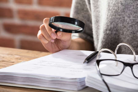 Close-up Of A Businesswoman Examining The Document Through Magnifying Glass On Wooden Desk
