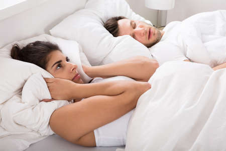 Annoyed Wife Blocking Her Ears With Pillow From Noise Of Husband Snoring