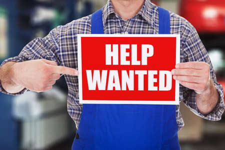 Close Up Of A Male Technician Showing Help Wanted Sign Stock Photo