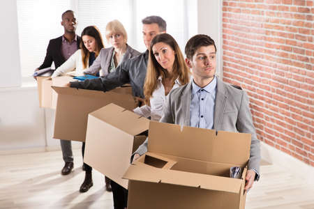 Row Of Diverse Businesspeople Standing With Cardboard Boxes In Office Stock Photo