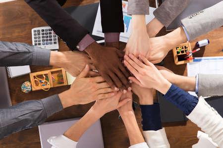 기업인들이 회의에서 서로의 손을 꼭대기에 올려 놓는 모습 스톡 콘텐츠