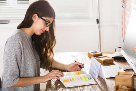 Young Businesswoman Writing Schedule In Diary With Calendar On Desk