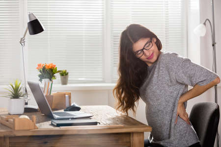 Young Attractive Businesswoman Having Back Pain In Office Stock Photo