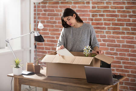 Sad Fired Young Employee Packing A Box To Leave The Office