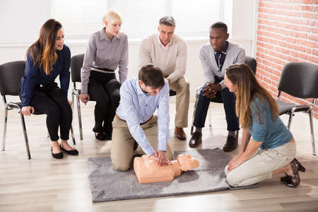 revive: First Aid Instructor Showing Resuscitation Technique On Dummy Stock Photo