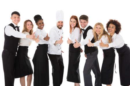 흰색 배경에 대해 몸짓으로 레스토랑 직원을 웃고 엄지 손가락