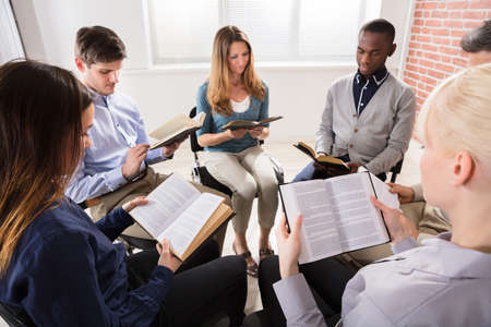 Group Of People Sitting On Chair In Circle Reading Bibles Stock Photo - 79443364