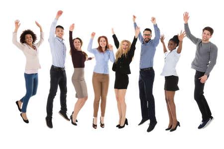 Retrato de estudiantes universitarios emocionados levantando sus armas sobre fondo blanco