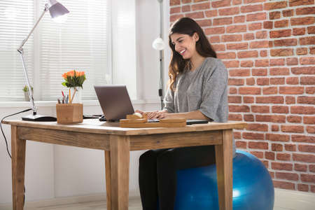 Happy Young Businesswoman Sitting On Fitness Ball Using Laptop In Office Stock Photo