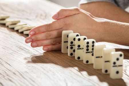 Close-up Of A Businesswoman Stopping Domino From Falling On Wooden Desk Imagens - 79443258