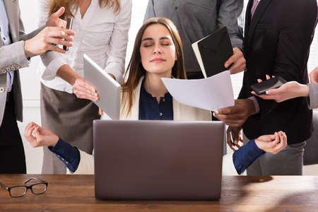 Joven empresaria rodeada de manos que le dan mucho trabajo en la oficina