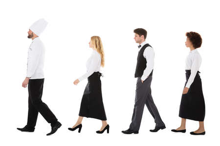 hotel staff: Young Restaurant Staff Walking In Row Against White Background