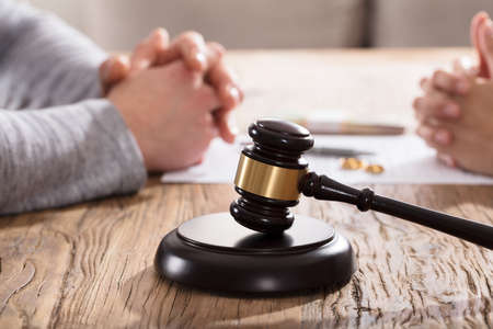 Gavel In Front Of Couples Hand On Wooden Table Stock Photo