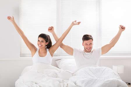 Sonriente joven pareja con su brazo levantado sentado en la cama por la mañana