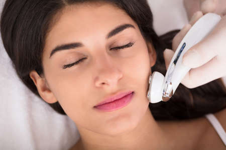 Close-up Of A Therapist Giving Needle Free Mesotherapy Treatment On Womens Face