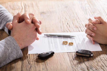 Hands On Divorce Document With Wedding Rings And Car Keys On Table