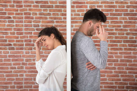 Depressed Contemplated Young Couple Against Brick Wall Stock Photo