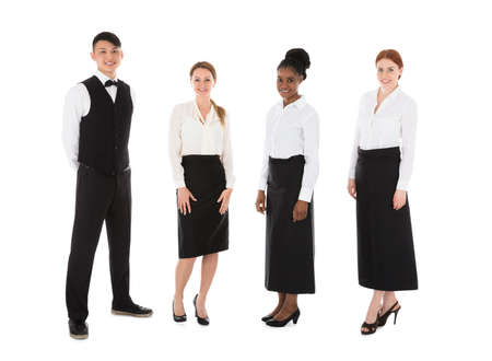 Portrait Of Happy Young Restaurant Staff Standing Over White Background Stock Photo