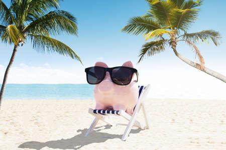 Piggybank met zonnebril op Ligstoel genieten van de vakantie op het strand Stockfoto - 79920599