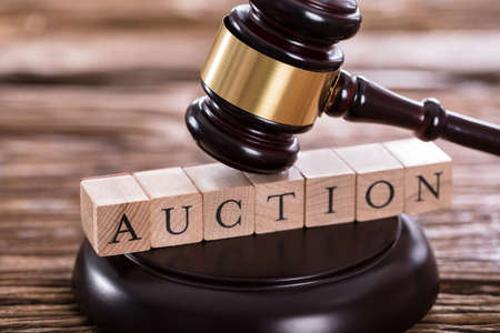 bidder: Close-up Of A Gavel Striking On Auction Word