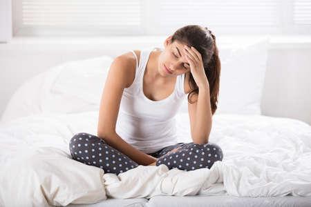 In Betracht gezogene junge Frau, die auf zerknittertem Bett im Schlafzimmer sitzt