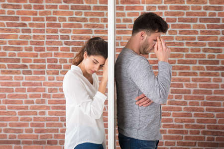 contemplated: Depressed Contemplated Young Couple Against Brick Wall Stock Photo