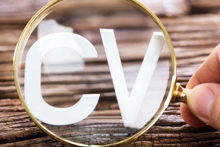 A Person Looking At White CV Word Through Magnifying Glass Stock Photo