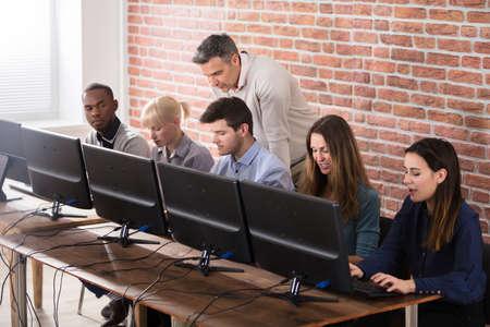 Groupe de cinq jeunes étudiants avec un enseignant masculin dans l'école d'informatique Salle de classe