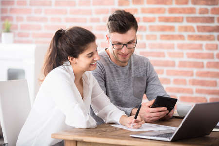 Happy Young Couple Calculating Bills At Home Using Calculator And Laptop