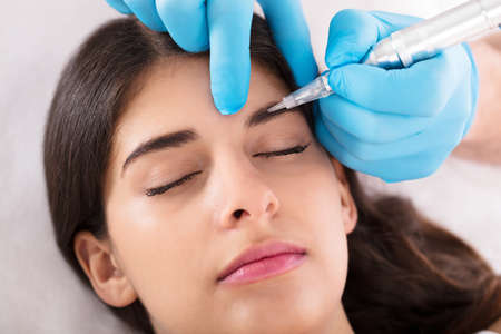 Cosmetologist Applying Permanent Make Up On Womans Eyebrows In Beauty Spa