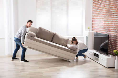 Young Happy Couple Placing Sofa At Their New Home
